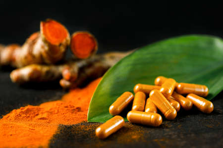 Turmeric powder in capsules, with fresh turmeric heads as a backdrop