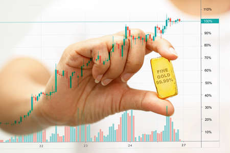 Woman hand holding a gold bar with a candlestick chart overlay