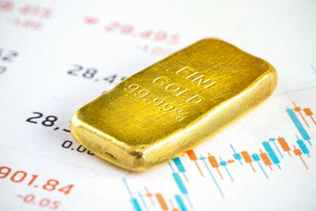 Gold bar placed on the investment  chart report. Stockfoto
