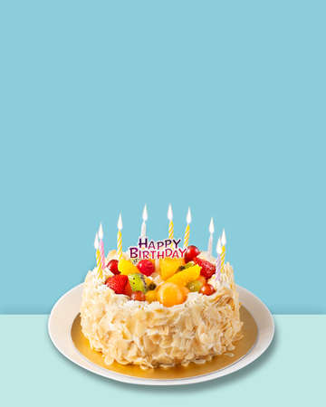 Happy birthday Fruit cake with almonds cream isolated on blue background. Stockfoto