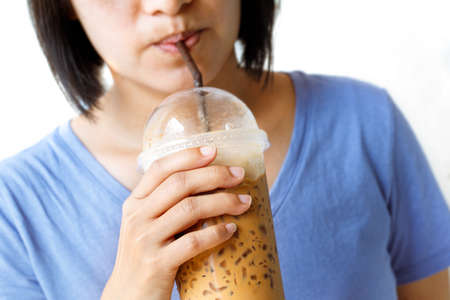 Asian woman drinking ice coffee by straw. Isolated white background.