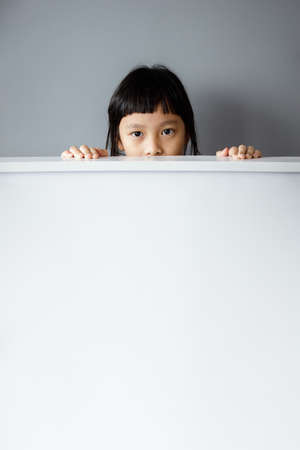 Asian girl hiding behind a blank board on a grey background.