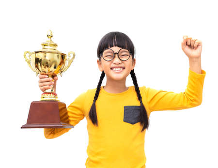 A young Asian girl held a gold trophy and expressed joyfully. Isolated on white background Stockfoto