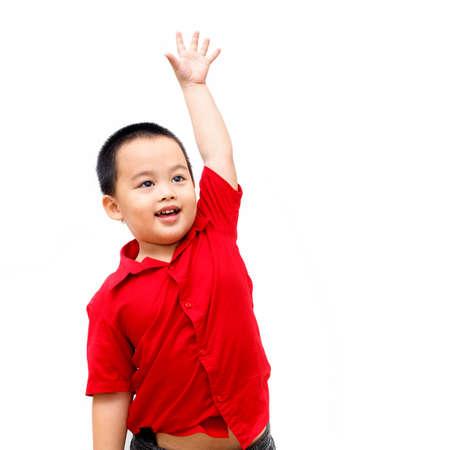 Little kindergarten boy raised his hand on a white backdrop
