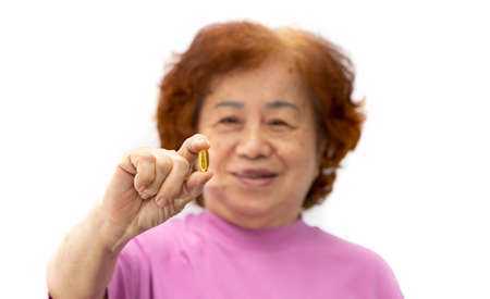 The senior woman held the Ffsh oil pill in hand. Isolated on white background