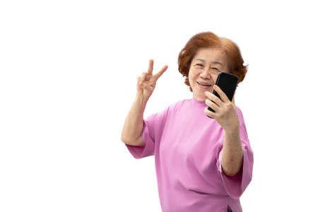 Grandma took a selfie picture with a mobile phone and posing with v-sign fingers. Isolated on white background Stockfoto