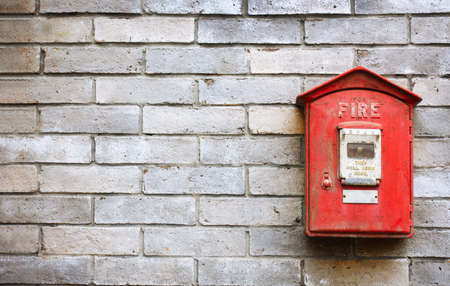 Vintage red fire alarm box on the old brick wall