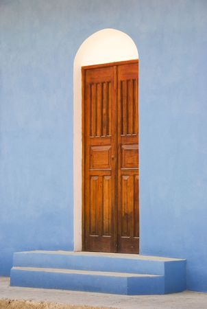 A lone door through a blue wall.