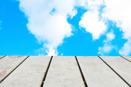 Old Wooden table with blue sky white cloud background.