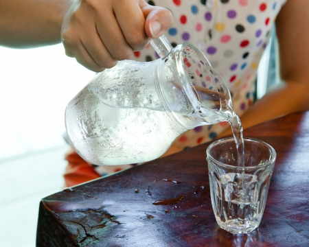 Pour water from a pitcher into a glass  Stock Photo