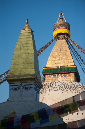 Prayer flags flying against the sun from the Boudhanath Stupa - symbol Kathmandu, Nepal.