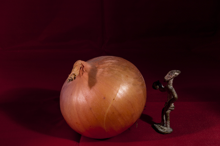 Still life fo onion and a figurine av a tribe man Stock Photo