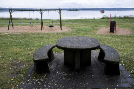 Stone furniture for outdoor dinne with playground and sea in the background