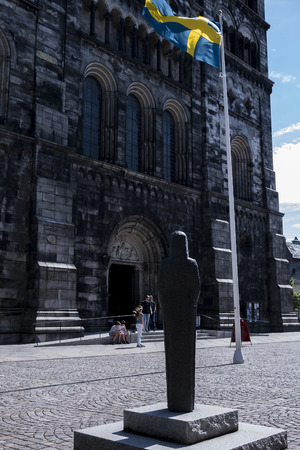 A statue and a flag n front of the dome in Lund, Sweden. Banco de Imagens