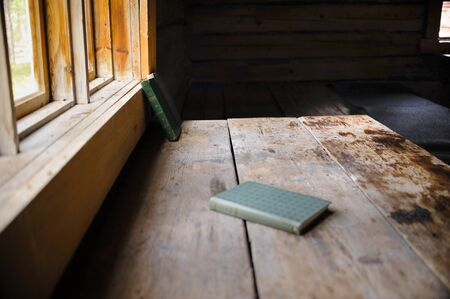 Two old books on an old table alight of the sun from the window in an ancient house