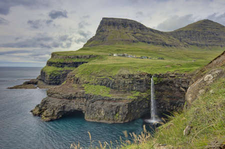 waterfall in the city: The village Gasadalur is surrounded by high mountains and the clear blue Atlantic on the island Vagar.