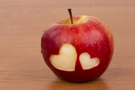 Two hearts on the fresh apple, a Valentine theme - on the wooden background photo