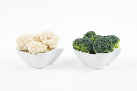 Fresh broccoli and cauliflower in a porcelain bowls photo