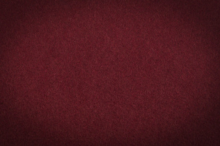 maroon: Maroon paper background or texture with vignette