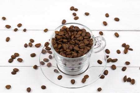 Coffee beans in the cup on a wooden background photo