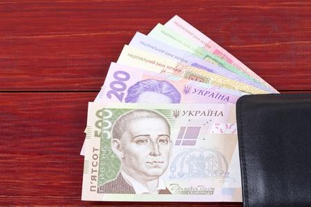 Ukrainian money in the black wallet Фото со стока
