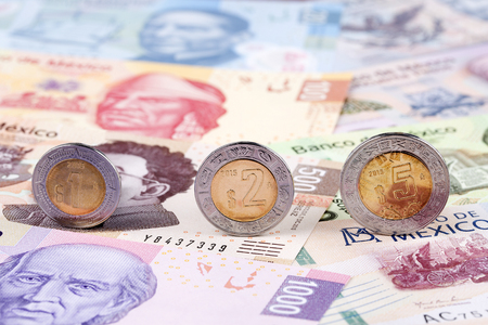 Mexican Peso coins on the background of banknotes