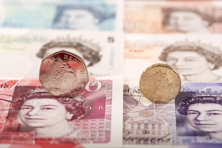 English pound coins on the background of banknotes