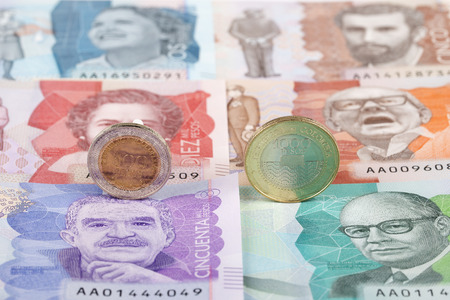 Colombian Peso coins on the background of banknotes