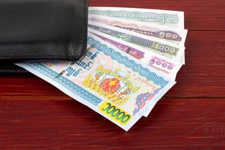 Burmese Kyat in the black wallet Stock Photo - 119613407