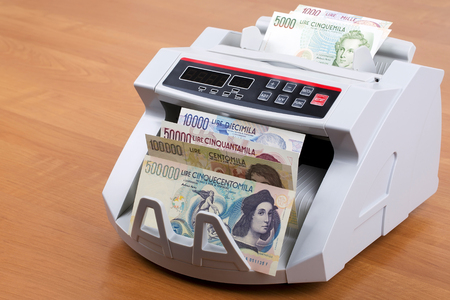 Italian Liras in a counting machine Stock Photo