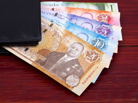 Tongan money in the black wallet Stock Photo - 129950976