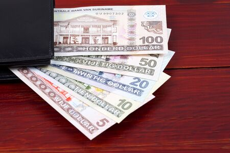 Surinamese Dollar in the black wallet Stock Photo