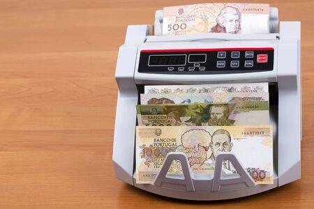 Old Portuguese Escudo in a counting machine Banco de Imagens