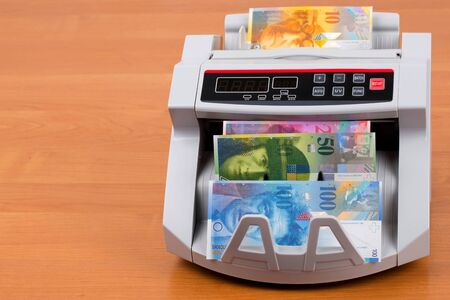 Swiss Francs in a counting machine Stock Photo