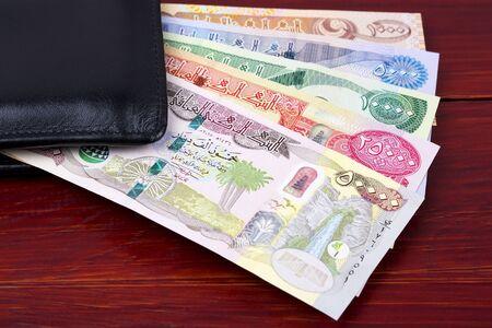 Iraqi money - Dinar in the black wallet Foto de archivo