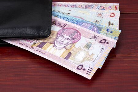 Money from Oman - Rial in the black wallet Stock Photo - 139899675