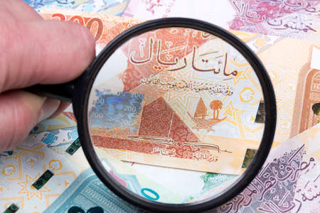 Money from Qatar in a magnifying glass a business background Stock Photo