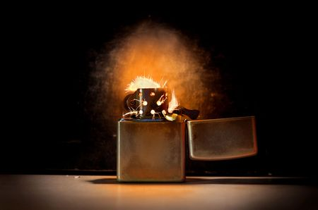 endure: spark lighter on black background (hands free) Stock Photo