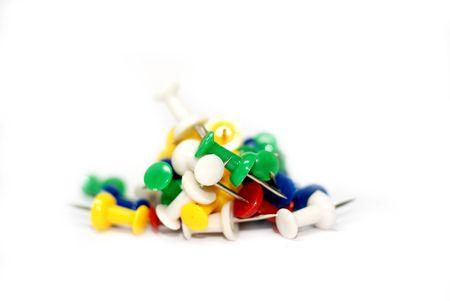 Multicoloured push pins on white background