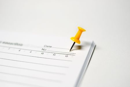 Isolated yellow push pin on white notebook Stock Photo - 4652231