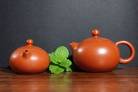 Asian teapot with sprigs of mint for tea