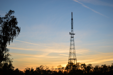 treeline: Steel radio tower with trees on the left and bottom at sunset coloring the sky blue and orange Stock Photo