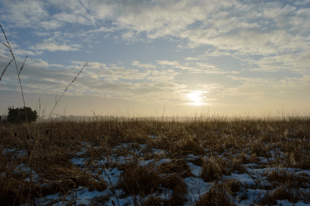 Sun rising on a cold morning melting the snow and creating drops of water on the brown grass in the foreground