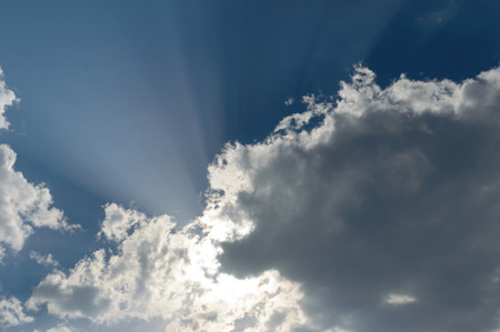 Rays from the sun breaking trhough the dark storm clouds filling the blue sky Zdjęcie Seryjne