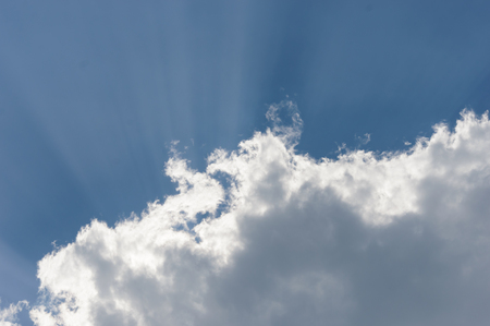 Clouds taking a blue sky lit by the sun casting rays from behind the clouds