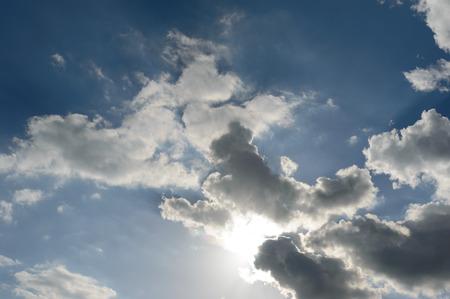 Sun light breaking through dark storm cloud formations taking a bleu sky Zdjęcie Seryjne
