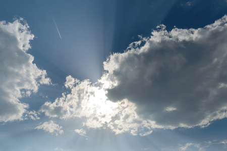 Sun casting god light rays at the camera faning out in all directions from behind the dark clouds Zdjęcie Seryjne