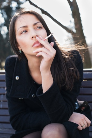 Young woman smokes on the street Stock Photo - 9321737