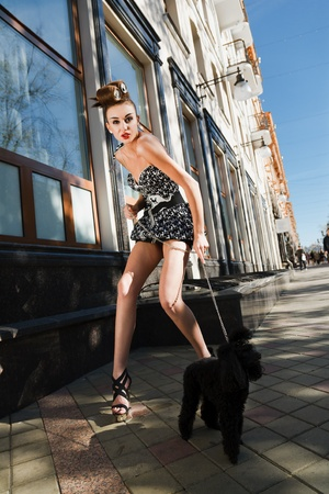 A girl with a dog standing on the street photo