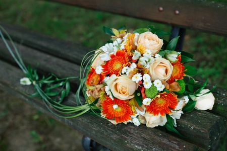 A wonderful bridal bouquet on a park bench. Stock Photo